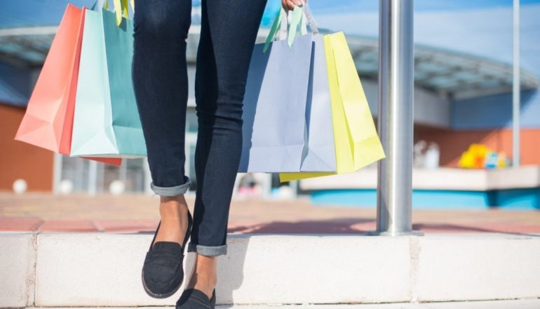 Woman walking out from a shopping mall with colourful shopping bags